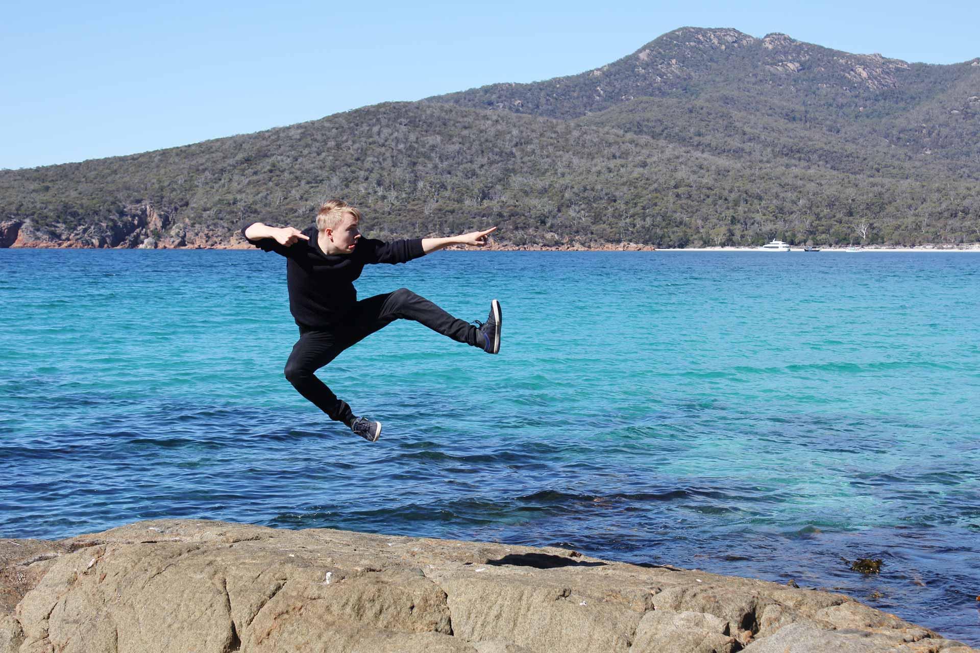 Mattias kicking the air at Wineglass Bay Tasmania